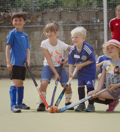 Kids, youngsters, juniors playing hockey at a sports summer camp